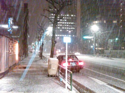 Taxi on a snowy Tokyo street at night.