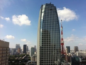 Tokyo Tower on a clear sunny day. Atago Green Hills office building is in the foreground.