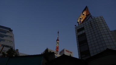 The very top of Tokyo Tower peaking above nearby buildings.