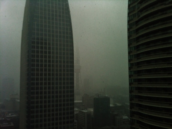A view of Tokyo Tower during a snow storm, with the Atago Green Hills office building in the foreground.
