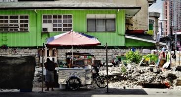 Manila street food vendor crumbled building