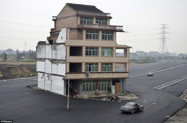 Chinese house in the middle of a highway